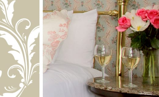 Victorian Village Suite room detail bed and side table with flowers and wine glasses